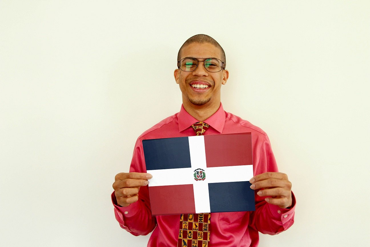 a smiling male f.d.m consultant holding a picture of a flag
