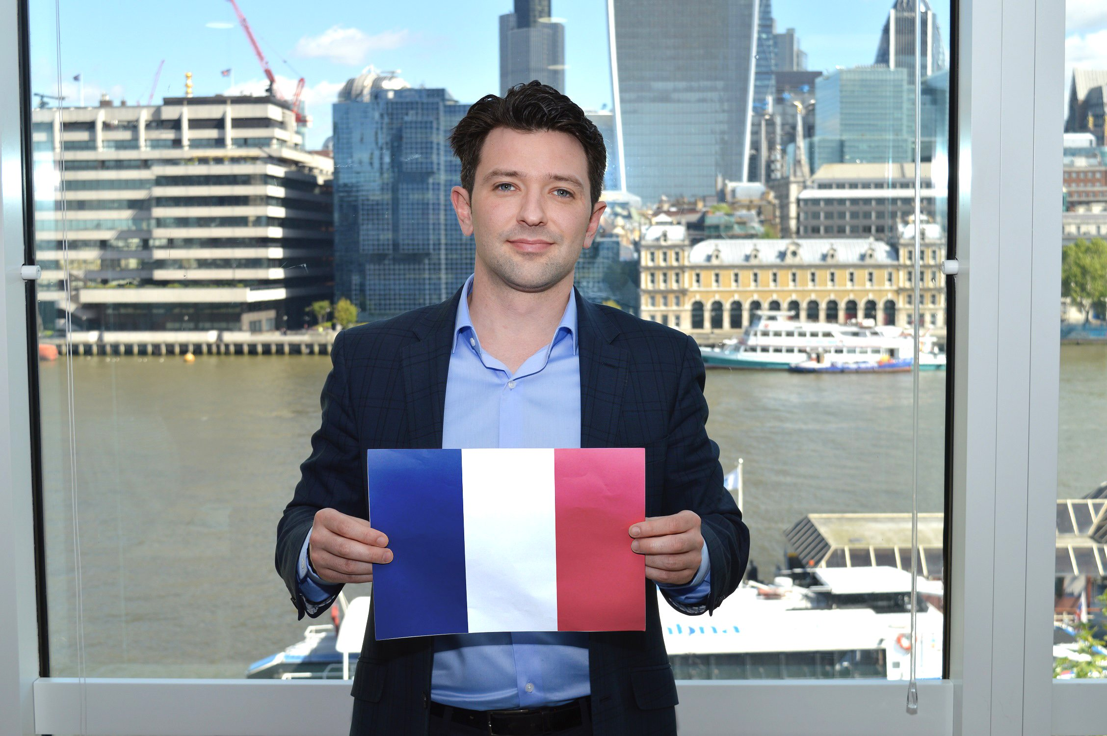 a male f.d.m. consultant holding a copy of the french flag