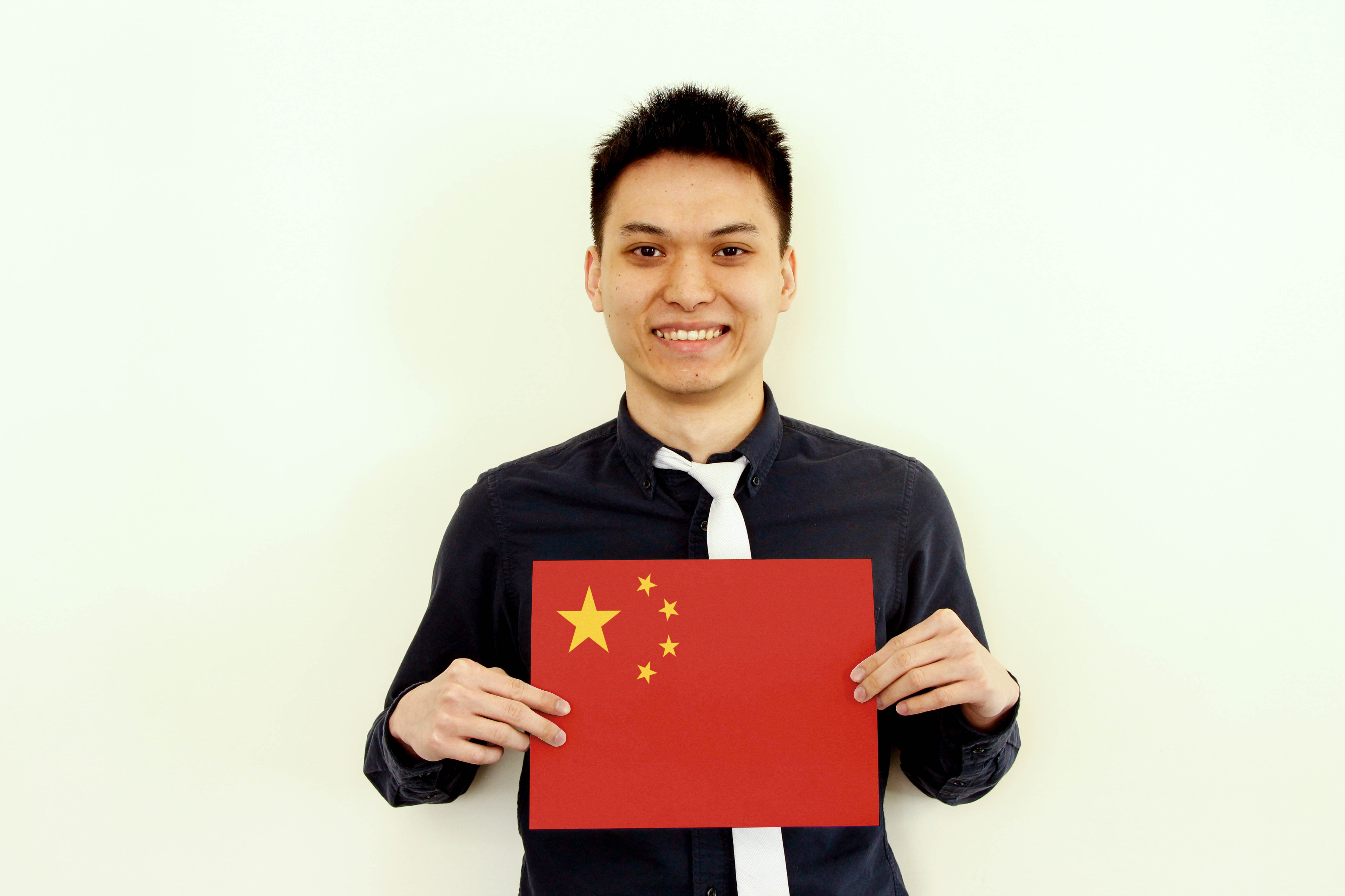 a male f.d.m. consultant holding a picture of the Chinese flag