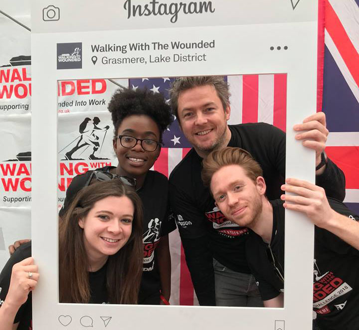 four f.d.m. colleages posing with a large cardboard Walking with the Wounded instagram frame cutout