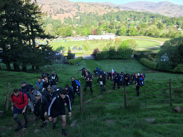 f.d.m. colleagues hiking up a steep grassy hill for a walking with the wounded charity race