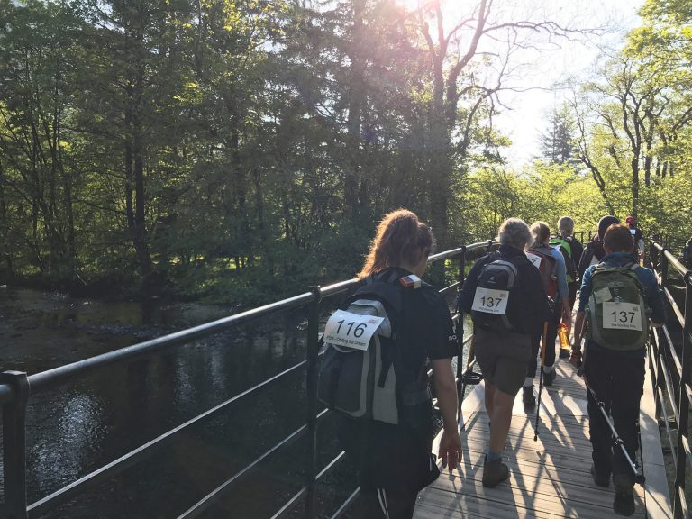f.d.m colleagues crossing a bridge over a river during a walking with the wounded charity race