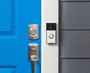 Stock photo of Amazon's Ring security device with a motion sensitive camera, next to a blue door.