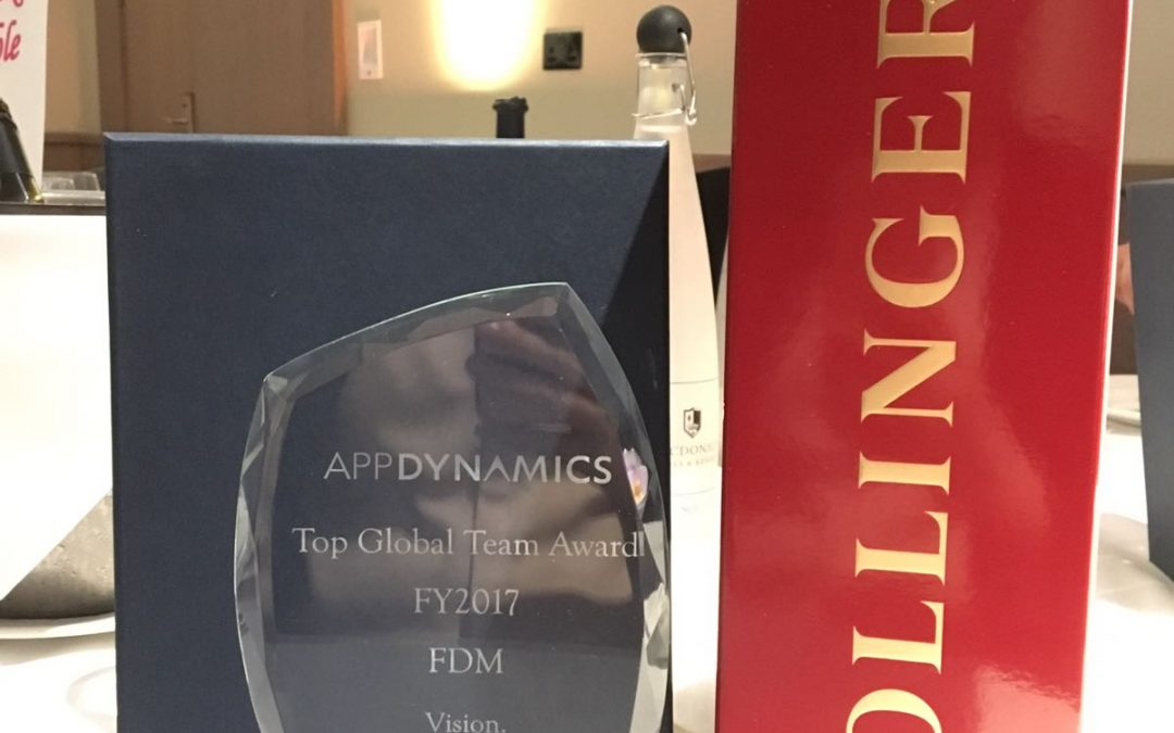 F.D.M.'s AppDynamics award next to a bottle of champagne.