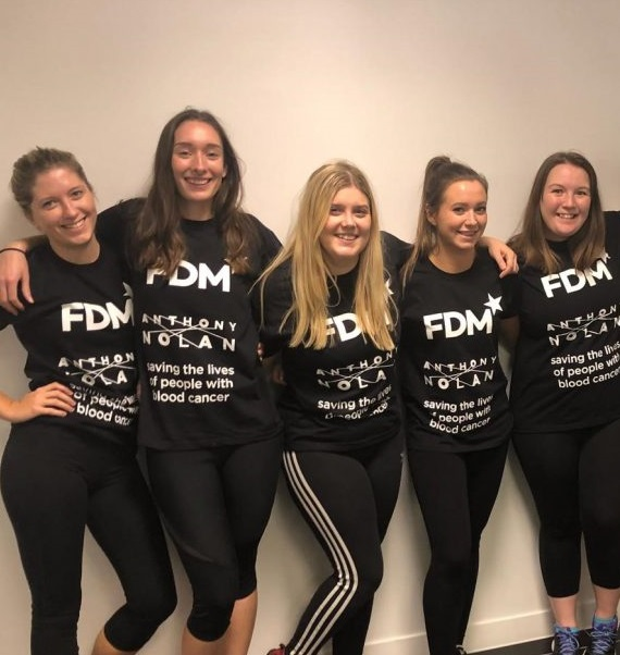 five young women wearing Anthony Nolan t-shirts standing together with their arms around each other's shoulders
