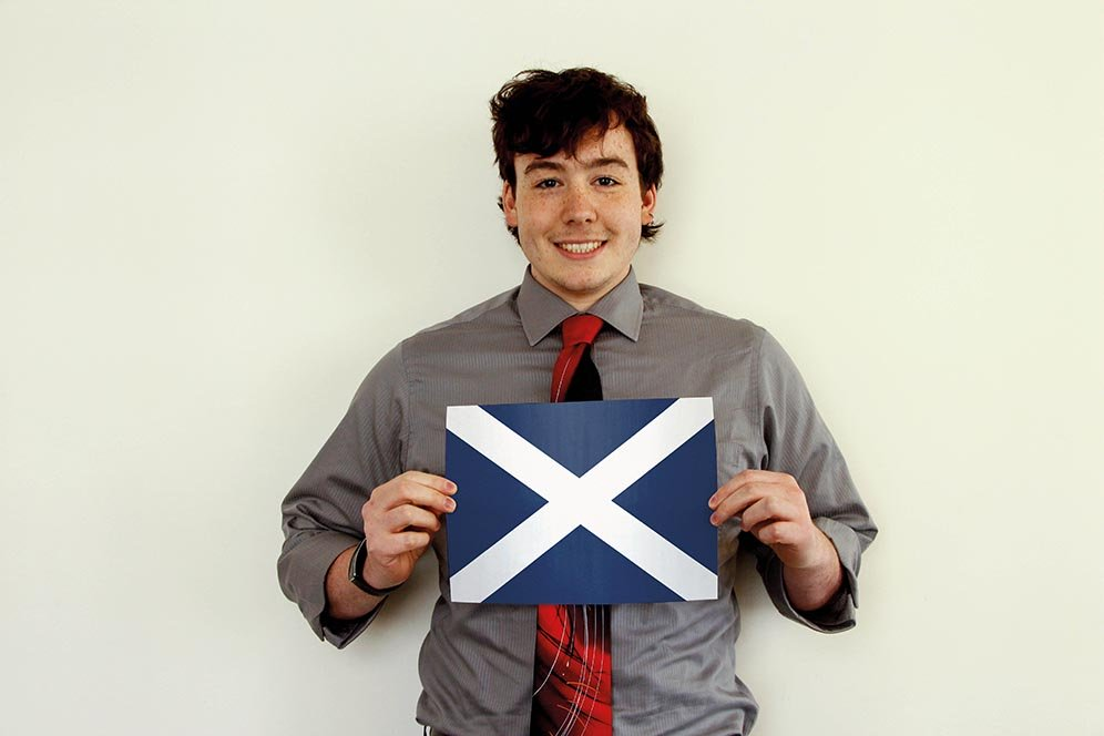 a male f.d.m. consultant holding a picture of the Scottish flag