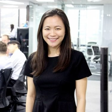 f.d.m. hong kong Consultant, Business Application Analyst Esther Ho wearing a dark blue business dress, standing against a busy office background