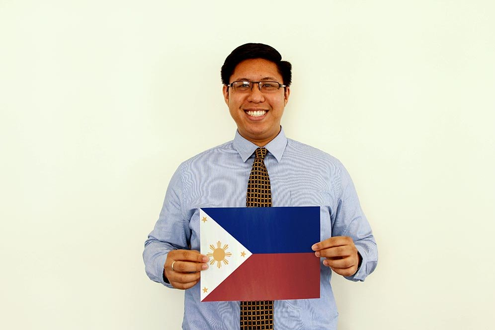 a male f.d.m. consultant holding a picture of the Filipino flag