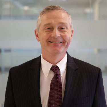 f.d.m. north america Head of Risk, Regulation and Compliance john plunkett wearing a dark pin stripe suit against a glass office background