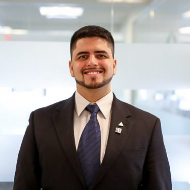 f.d.m Consultant, Core Application Services Junior Developer jordan paredes wearing a dark suit standing against a glass office background