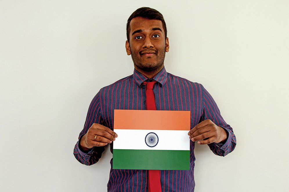 f.d.m. consultant java trainee Karthik Varadarajan standing against a white wall and holding a picture of the flag of India