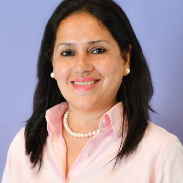 f.d.m. hong kong business trainer Mala Datta wearing a pink shirt, standing against a pale blue background