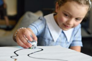 Image of a young girl tracing a small bot on paper