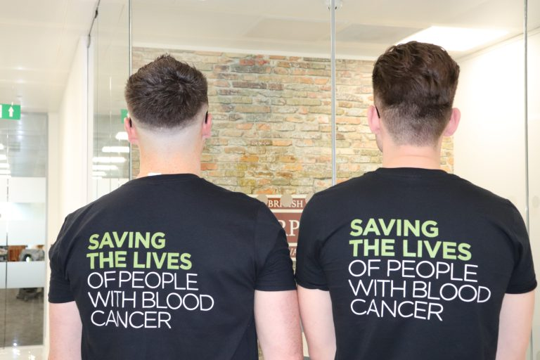 f.d.m. colleagues standing with their backs to the camera and wearing Anthony Nolan t-shirts with the slogan Saving the Lives of People with Blood Cancer