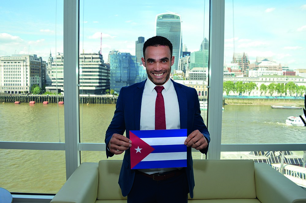 a smiling male f.d.m. consultant holding a picture of the cuban flag