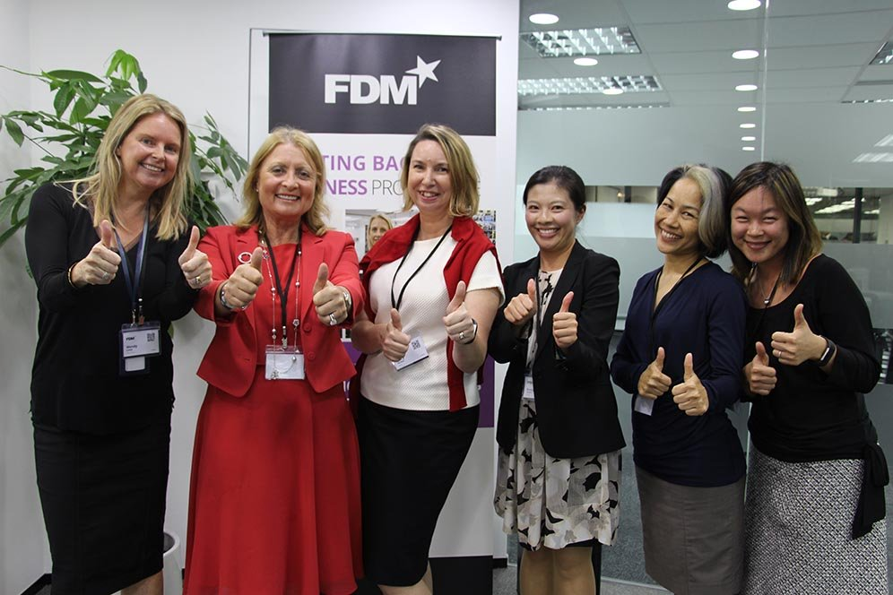 six women in business dress giving the thumbs up against an office background