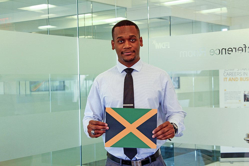 a male f.d.m consultant holding a picture of the Jamaican flag