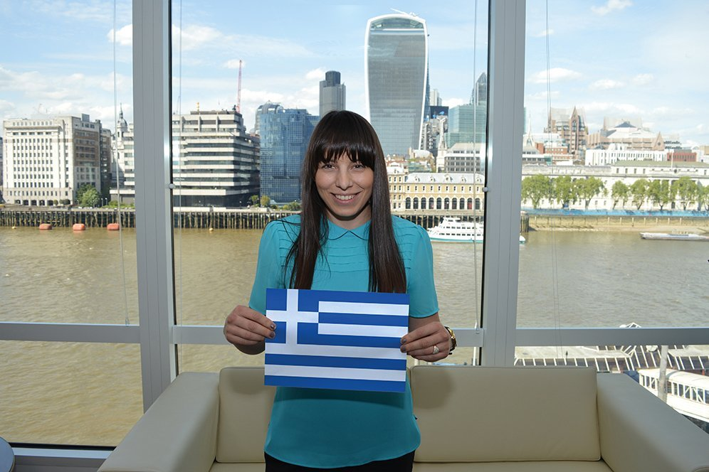 f.d.m. consultant Theodora Vakouftsi holding a picture of the Greek flag