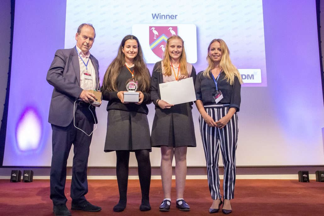 two f.d.m. colleagues standing on stage with two school girls collecting an award at the Teen Tech Awards