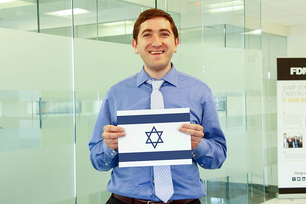 a male f.d.m. consultant holding a picture of the Israeli flag