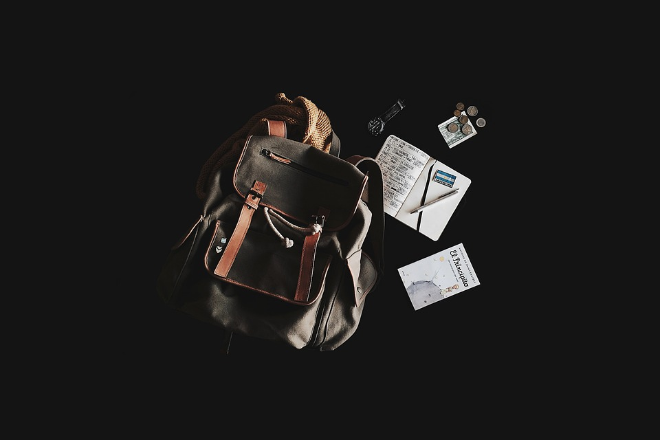 A backpack, book, coins and a watch against a black background.