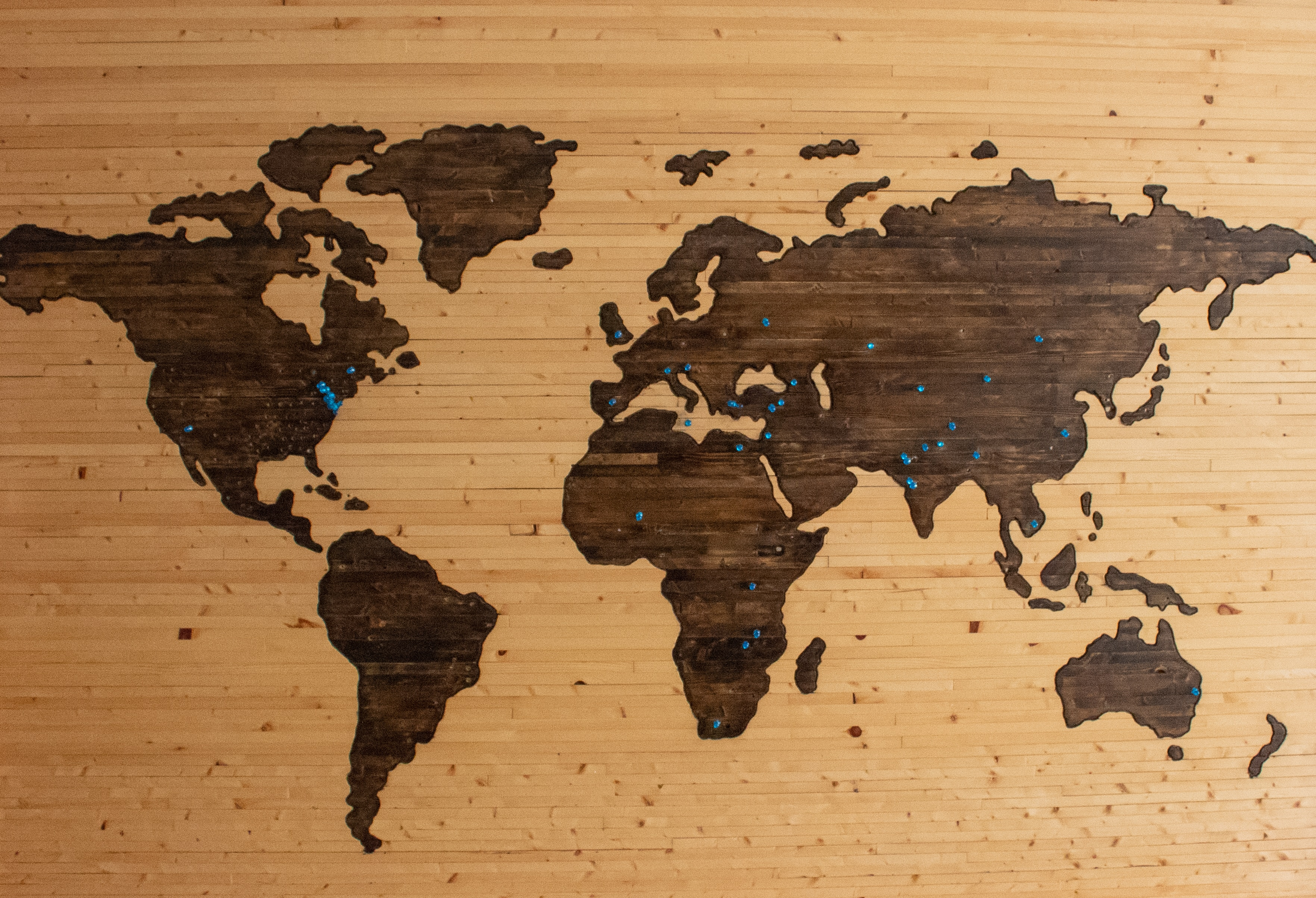 A world map against a brown sheet of wood with blue pins in certain places.