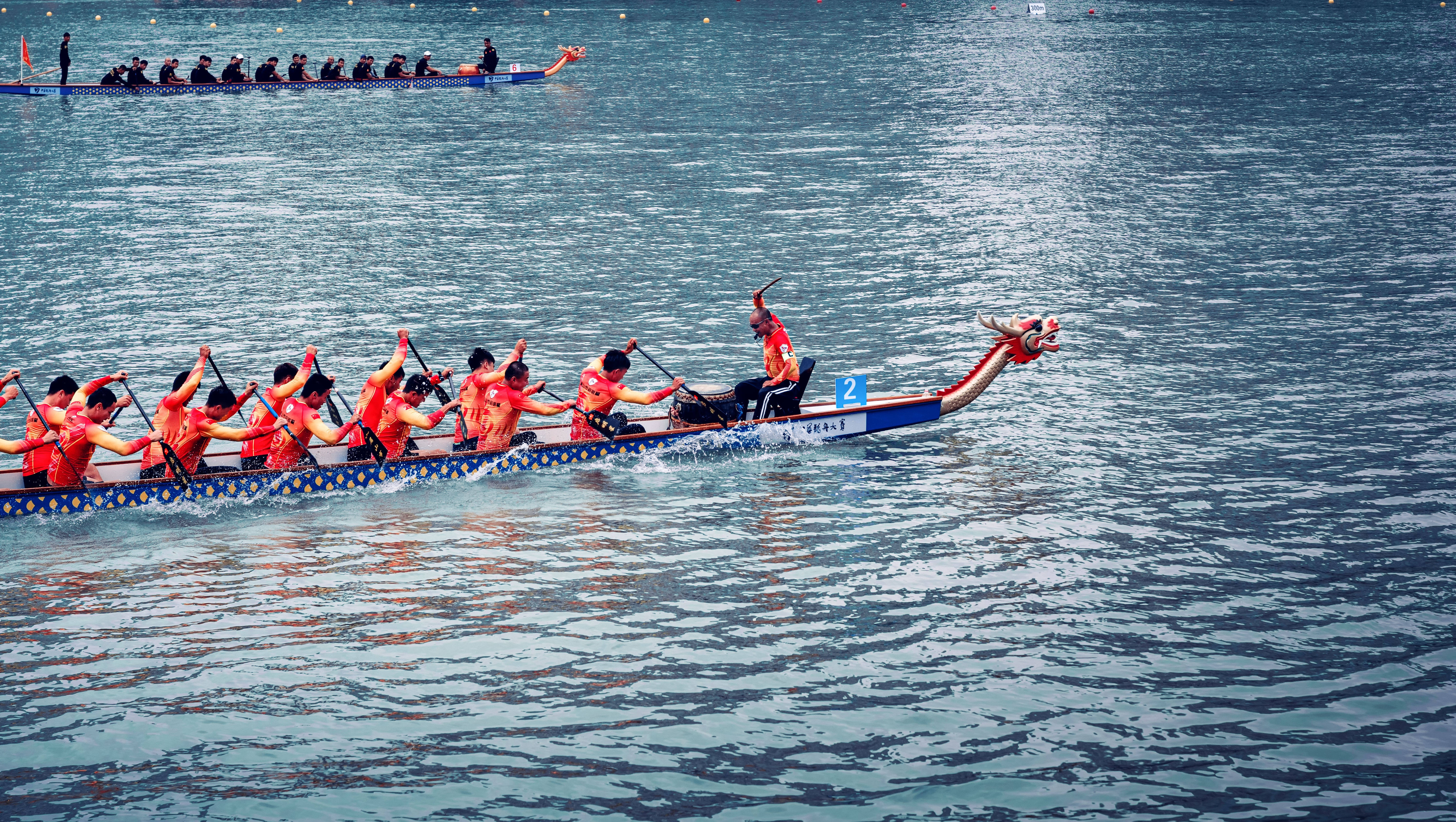 Dragon boat team paddling in the water in a red uniform.