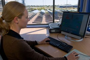 A female employee of the National Solar Energy Centre Tania Ritchie works at a computer with the solar panel field visible in the background, out the window.