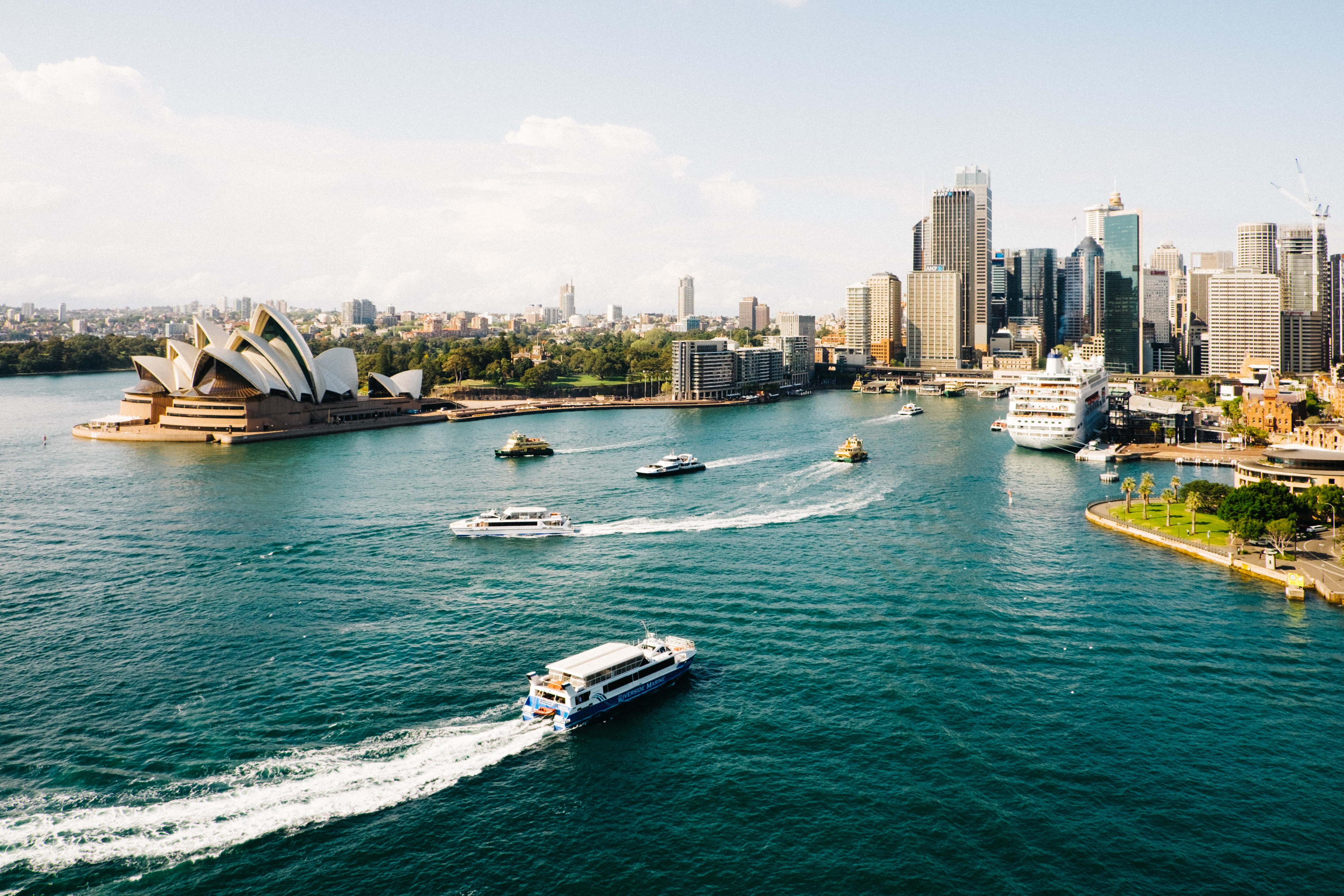 Aerial view of Sydney, Australia, with a boat racing towards the city.
