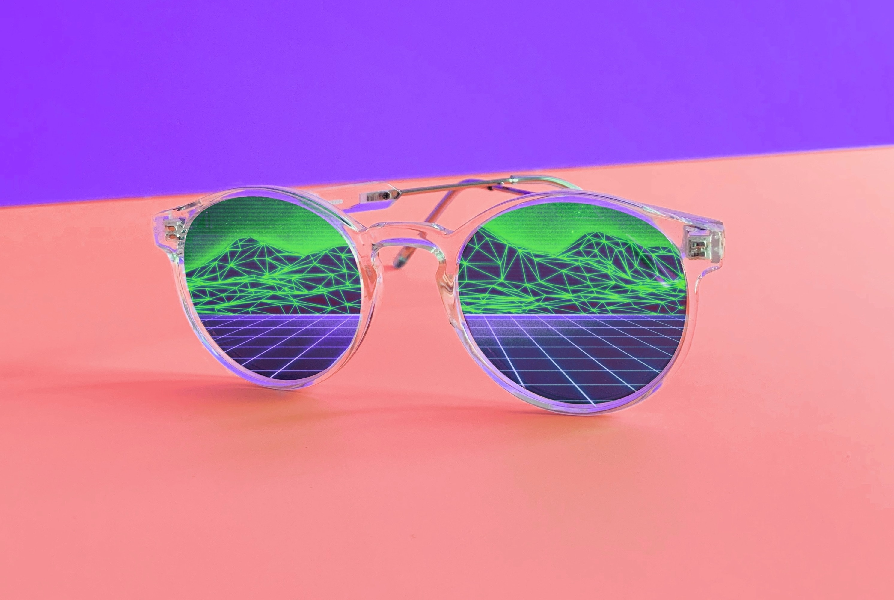 Metallic, reflective glasses in front of a purple and pink background.