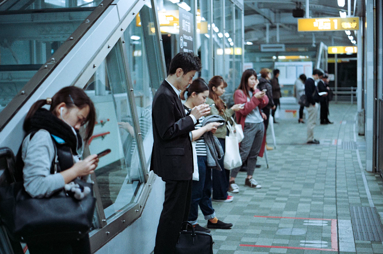 Profile view of commuters waiting for their transportation, distracted by their phones and looking down at them.
