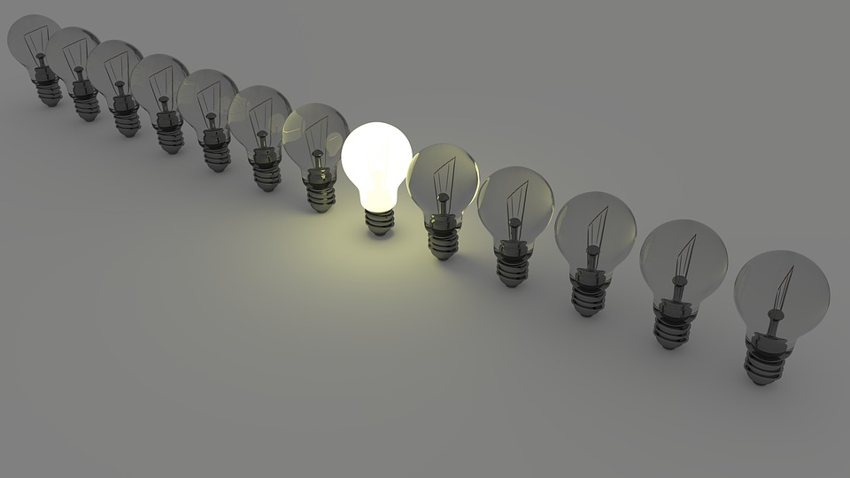 A row of light bulbs with only one lit against a grey background.
