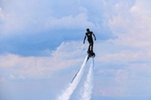 Man riding a flyboard mid-air with water jetting from the bottom of the device. Behind him is a cloudy, blue skies.