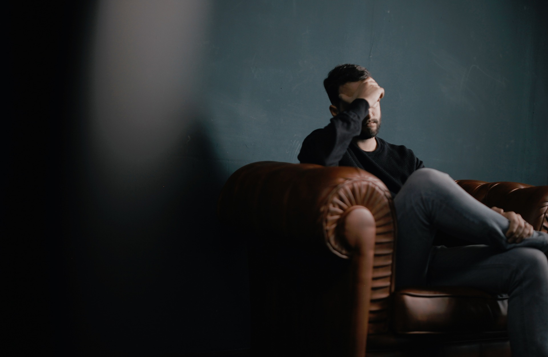 Man sitting on brown couch in a dark room holding his head, upset.