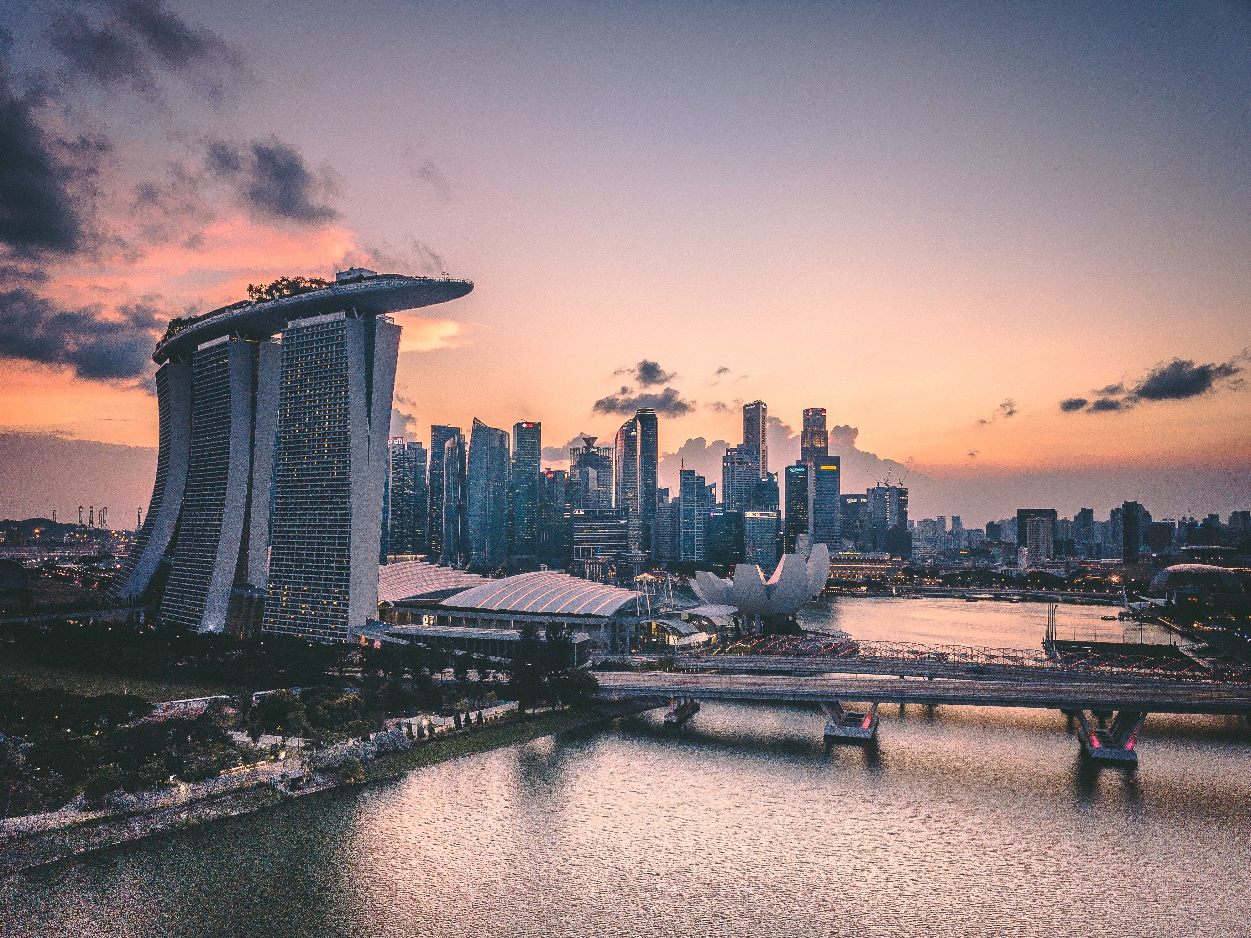 View of Singapore skyline and its surrounding body of water at sunset.