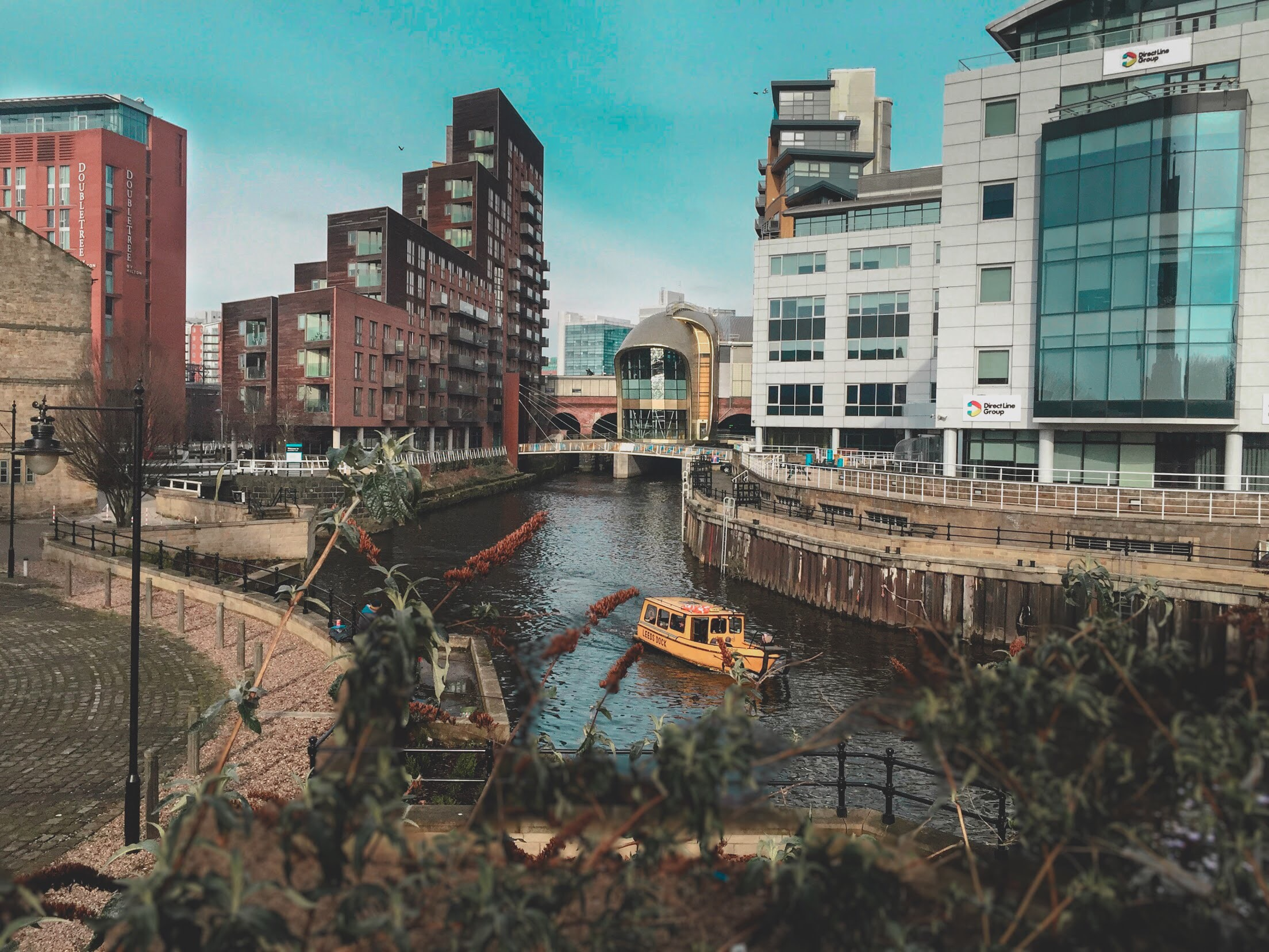 View of a canal and buildings in Leeds, United Kingdom, during mid afternoon.