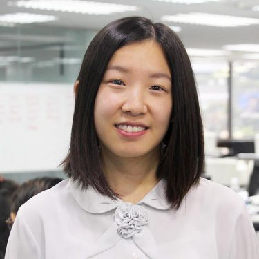 f.d.m. hong kong Consultant, Project Analyst Yoyo Fung in a white blouse standing against an office background